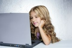 Student little school girl on laptop compute. Student little school girl doing homework on laptop computer in silver background stock photography