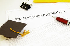 Student loan app. Lication form and mini graduation cap royalty free stock photos
