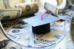 Student Loan Debt With Graduation Cap On Money Barrowed. Stock Photo stock photo