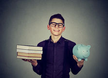 Student loan. Man with pile of books and piggy bank. Student loan concept. Happy man with stack pile of books and piggy bank full of debt royalty free stock photography