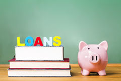 Student loan theme with textbooks and piggy bank Royalty Free Stock Image