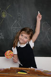 Student with lollipop. Young student girl near blackboard holding a piece of chalk and a lollipop stock image