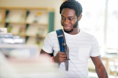 Student Looking At Books In Bookstore. Smiling young male student carrying backpack while looking at books in bookstore Royalty Free Stock Photos