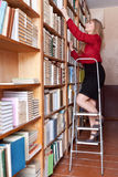 Student is looking books on the shelves standing on a ladder Stock Photo