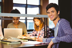 Student looking at camera with his classmates behind him. In library Royalty Free Stock Photography