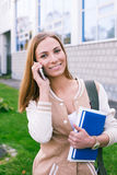 Student looking at camera. Student talking on phone and looking at camera stock photography