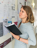 Student looking through job offers. Young female student looking through job offers on board Royalty Free Stock Images