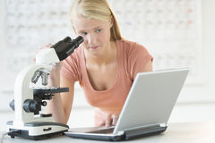Student Looking At Laptop While Using Microscope Stock Photos