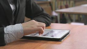 Student looking at photos using computer tablet. Close-up of hand of student boy dressed in black suit sits at desk at office the resting and looking at favorite stock footage