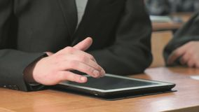 Student looking at photos using computer tablet. Close-up of hand of student boy dressed in black suit sits at desk at office the resting and looking at favorite stock video footage