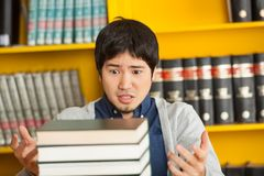 Student Looking At Pile Of Books In University. Shocked male student looking at pile of books in university library Royalty Free Stock Photography