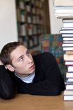 Student Looking Up At Pile of Books. A frustrated student looks up at the high pile of textbooks he has to go through to do his homework assignment Stock Photos