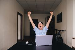 The student looks up and is glad to raise his hands up. Teen room. Happy student looking at a laptop and rejoicing while raising his hands up. Teen room Stock Photo