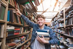 Student with a lot of books in his hands is in the library, takes books from the shelf and looks at the camera stock images