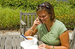 Student Lunch Outdoors. Woman enjoying lunch outdoors talking on cellphone while studying Stock Photo