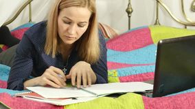 Student lying on a bed in home. woman working on her laptop. on-line education. 4K. Student lying on a bed in home. woman working on her laptop. on-line stock footage