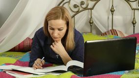 Student lying on a bed in home. woman working on her laptop. on-line education. slow motion. Student lying on a bed in home. woman working on her laptop. on-line stock footage