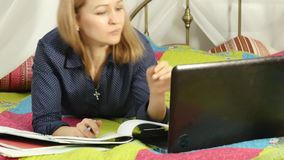 Student lying on a bed in home. woman working on her laptop. on-line education.  stock video