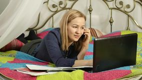 Student lying on a bed in home. woman working on her laptop. on-line education. slow motion. Student lying on a bed in home. woman working on her laptop. on-line stock video footage