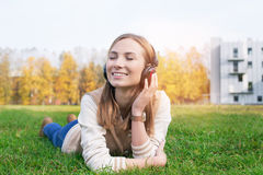 Student lying on grass and listening music into headphones. Student lying on green grass and listening music into headphones with closed eyes royalty free stock photo
