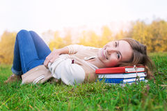 Student lying on green grass and books and looking up. On the sunset royalty free stock image