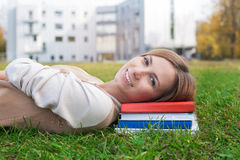 Student lying on green grass and books. On the sunset royalty free stock image