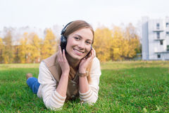 Student lying on green grass and listening to headphones. On the sunset stock photo