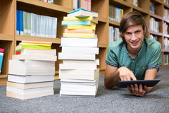 Student lying on library floor Royalty Free Stock Photos