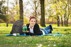 Student lying on a meadow holding a piggy bank Royalty Free Stock Photography