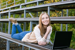 Student lying on sport tribune smiling and looking away. Student lying on sport tribune and smiling away stock photo