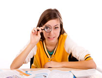 Student with magnify glass. Student at her desk with magnify glass isolated on white background Stock Image
