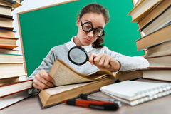Student with a magnifying glass seeks the answer in book. Photo of girl keen on reading book. Education concept royalty free stock photos