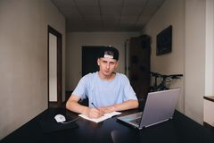 A student makes a homework job while sitting in his home. Teens study at home. A look at the camera. Teenager boy doing homework on his desk at home stock image