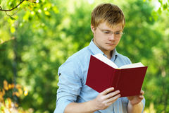 Student (male) with glasses reading Stock Photos