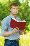 Student (male) with glasses reading book Stock Image