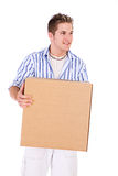 Student: Man With Packing Box Glances To Side. Series of a young man getting ready for college, with packing boxes and dorm room stuff Stock Image