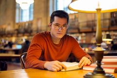 Student man reading book in library wearing eyeglasses Royalty Free Stock Photos