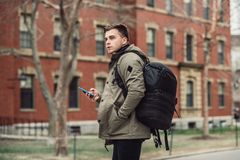 Student man text on cell phone walking in city college campus with backpack. royalty free stock photography