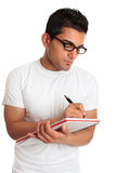 Student or man wearing glasses writing. An ethnic student or man wearing reading glasses is writing in a notebook Royalty Free Stock Images