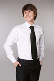 Student Man in white shirt with black tie keeping hands in pocke. Ts and smiling while standing against grey studio background Stock Photo