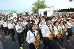 A Student Marching Band. KAOHSIUNG, TAIWAN -- OCTOBER 1, 2017: A student marching band joins a street parade at the opening of the 2017 Ecomobility Festival Royalty Free Stock Image