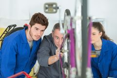 Student mechanics looking at bicycle with teacher stock images