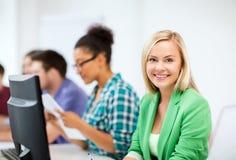 Student med datoren som studerar på skolan arkivbild