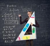 Student med en stor linjal och Pythagoreanteorem på svart tavla fotografering för bildbyråer