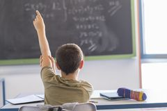 Student med händer upp i klassrum under en kurs Arkivbilder