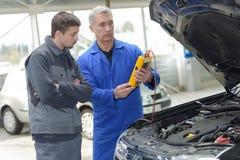 Student med instruktören som reparerar bilen under lärlingskap fotografering för bildbyråer