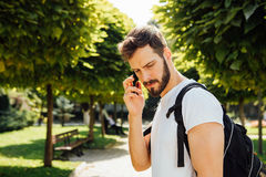 Student med ryggsäcken som talar på mobiltelefonen arkivfoto
