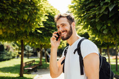 Student med ryggsäcken som talar på mobiltelefonen royaltyfri fotografi