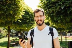Student med ryggsäcken som talar på mobiltelefonen arkivfoton