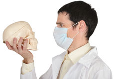 Student medical school in mask looks at skull Stock Photos